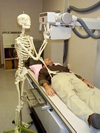 Skeleton taking an x-ray of a man.